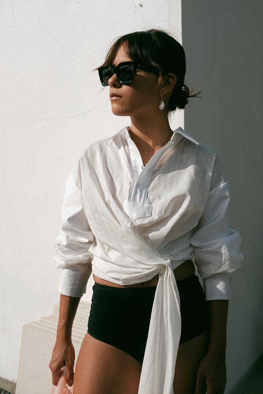 Nisi is wearing: Jacquemus La chemise Nodoso Blouse, Cult Gaia Ark bag, Adidas slides, Celine Kate sunglasses