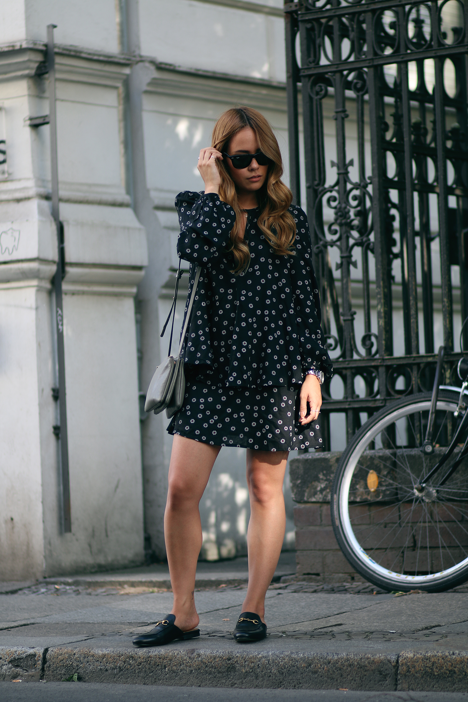 Desi is wearing: Gucci Princetown Slipper, flower dress, Céline Trio bag, Ray-Ban Wayfarer sunglasses