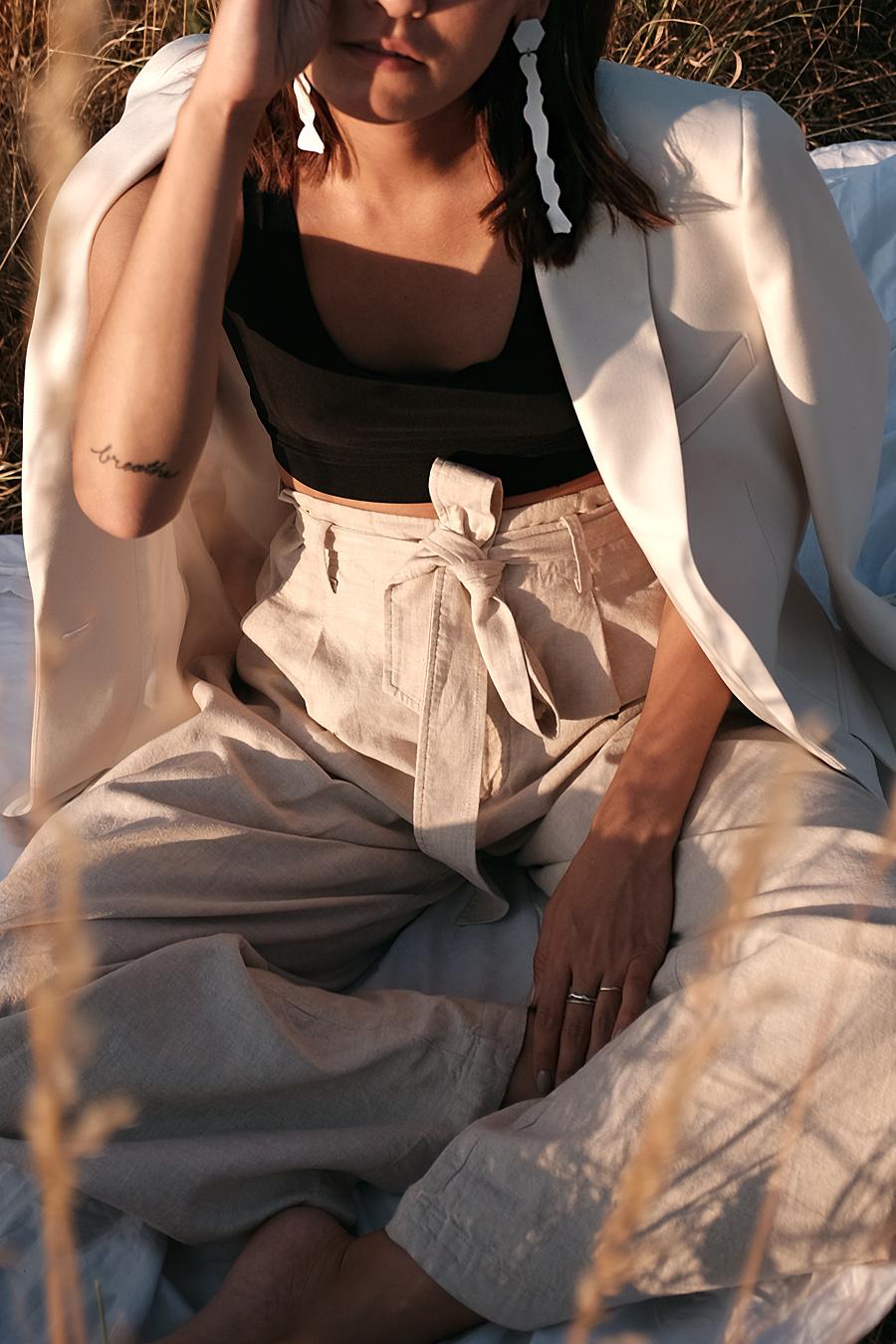 Nisi is wearing: Uniqlo linen paperbag trousers, Arket White blazer, Chanelle black bralette, Mango white statement earrings