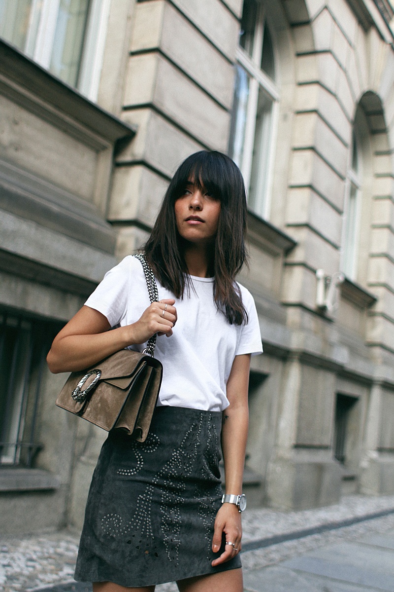 Nisi is wearing: Gucci Dionysus bag, Hermès Oran Sandals, studded suede skirt and a basic white t-shirt from Acne Studios