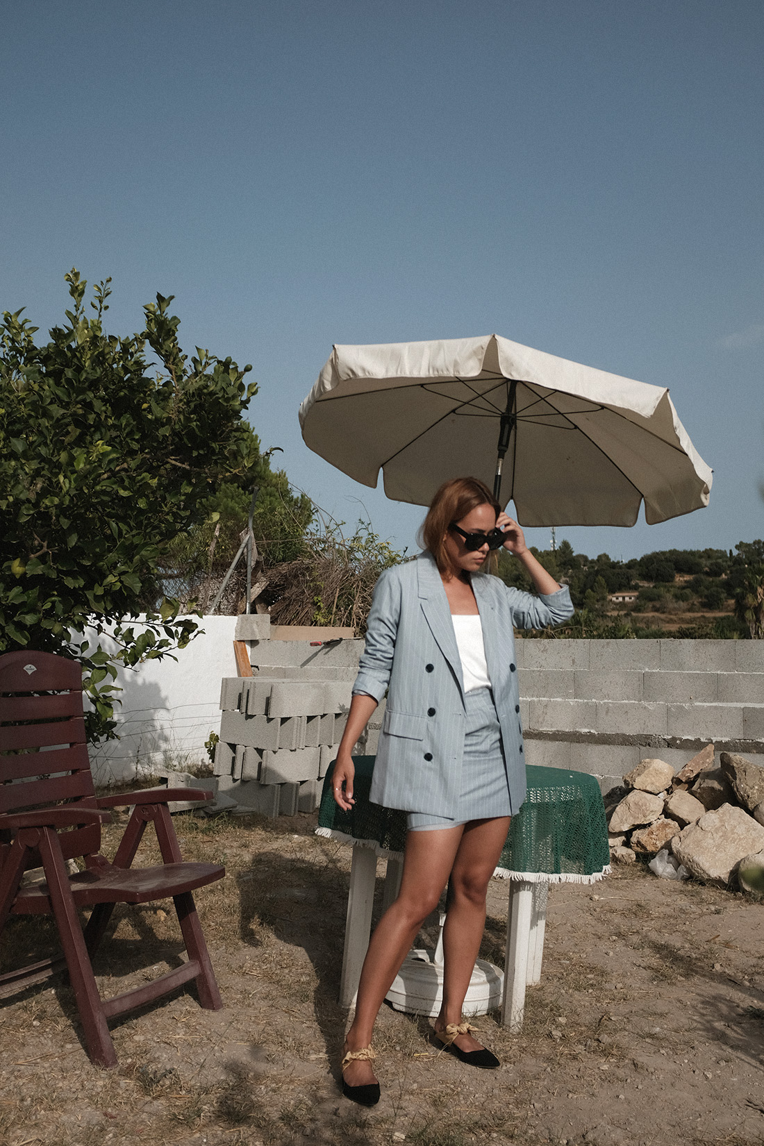 Desi is wearing: The Row Bow mules, Céline Sunglasses, Edited the Label Pinstripe blazer and pinstripe pencil skirt, Edited the Label silky white camisole