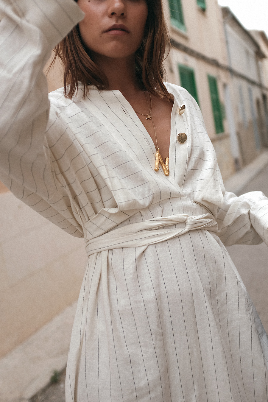 Nisi is wearing: The Row Ascot bag,  Céline Alphabet necklace, Striped dress, Black strappy sandals, Coral necklace, Gold pearl earring