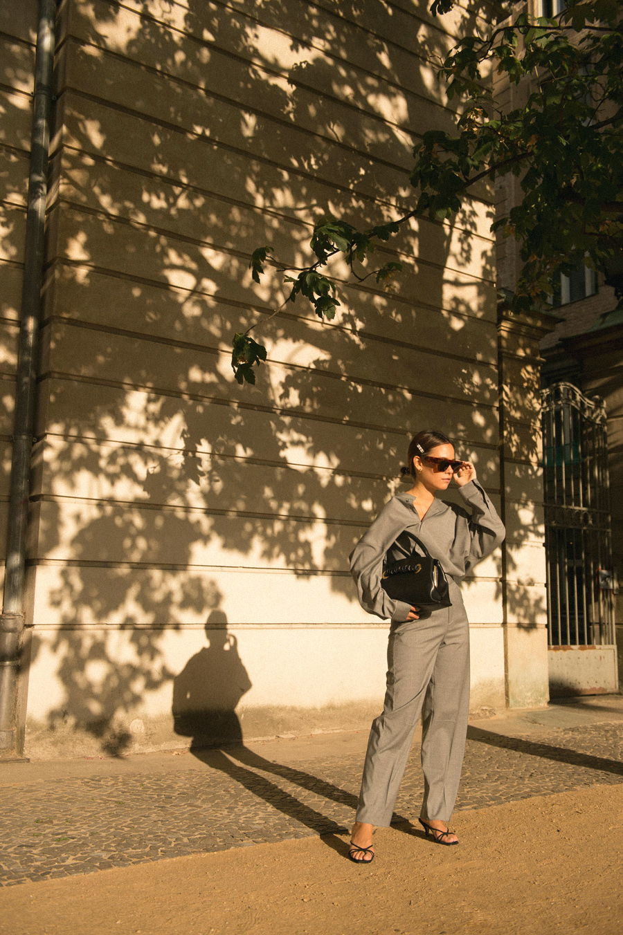 Nisi is wearing: Totême Grey shirt and trousers, Céline Purse with Eyelets bag, Strappy sandals, Céline Sunglasses, Pearl hair clip