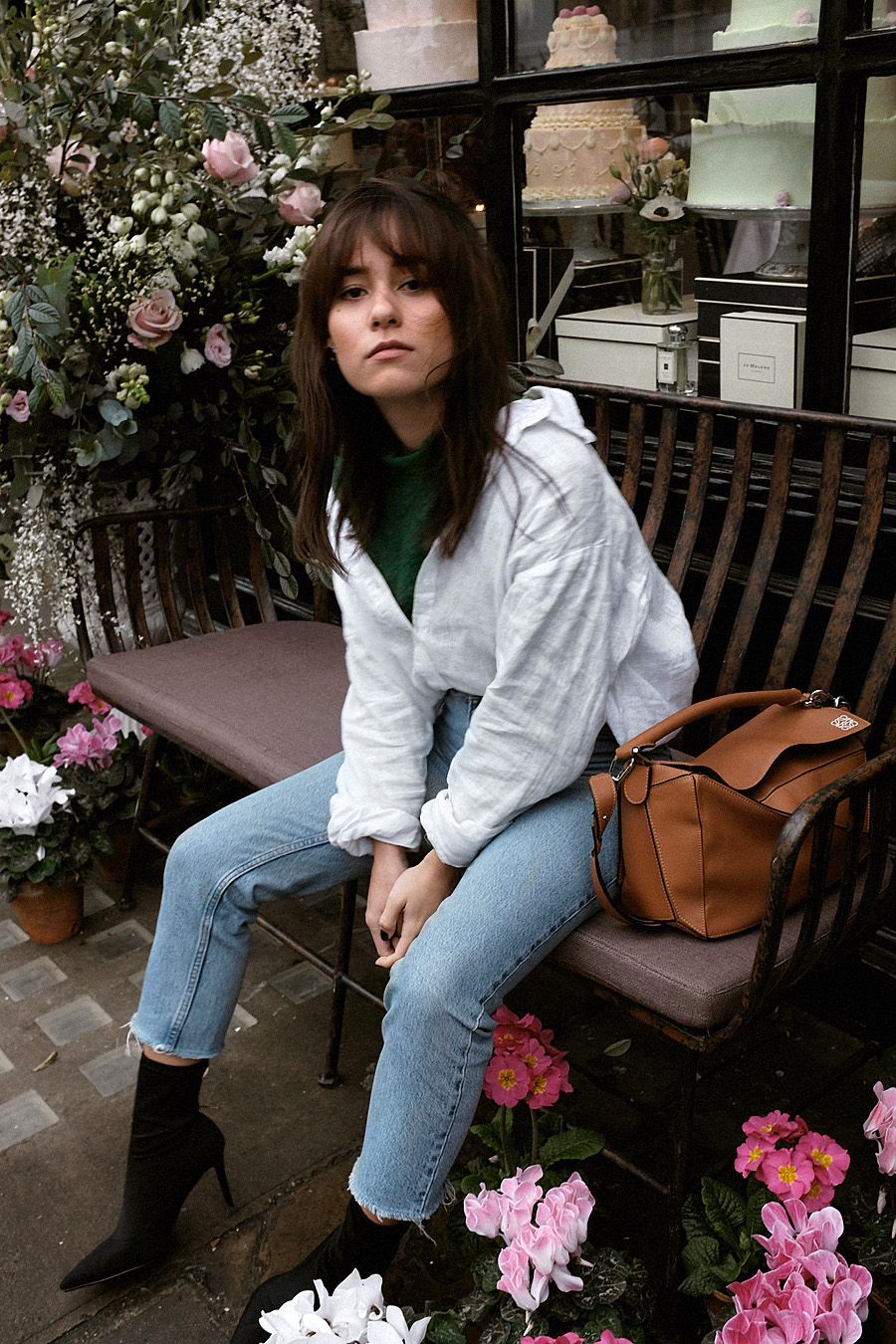 Nisi is wearing: Loewe Puzzle bag, Green lace top, White shirt, Mom jeans, Stretch boots